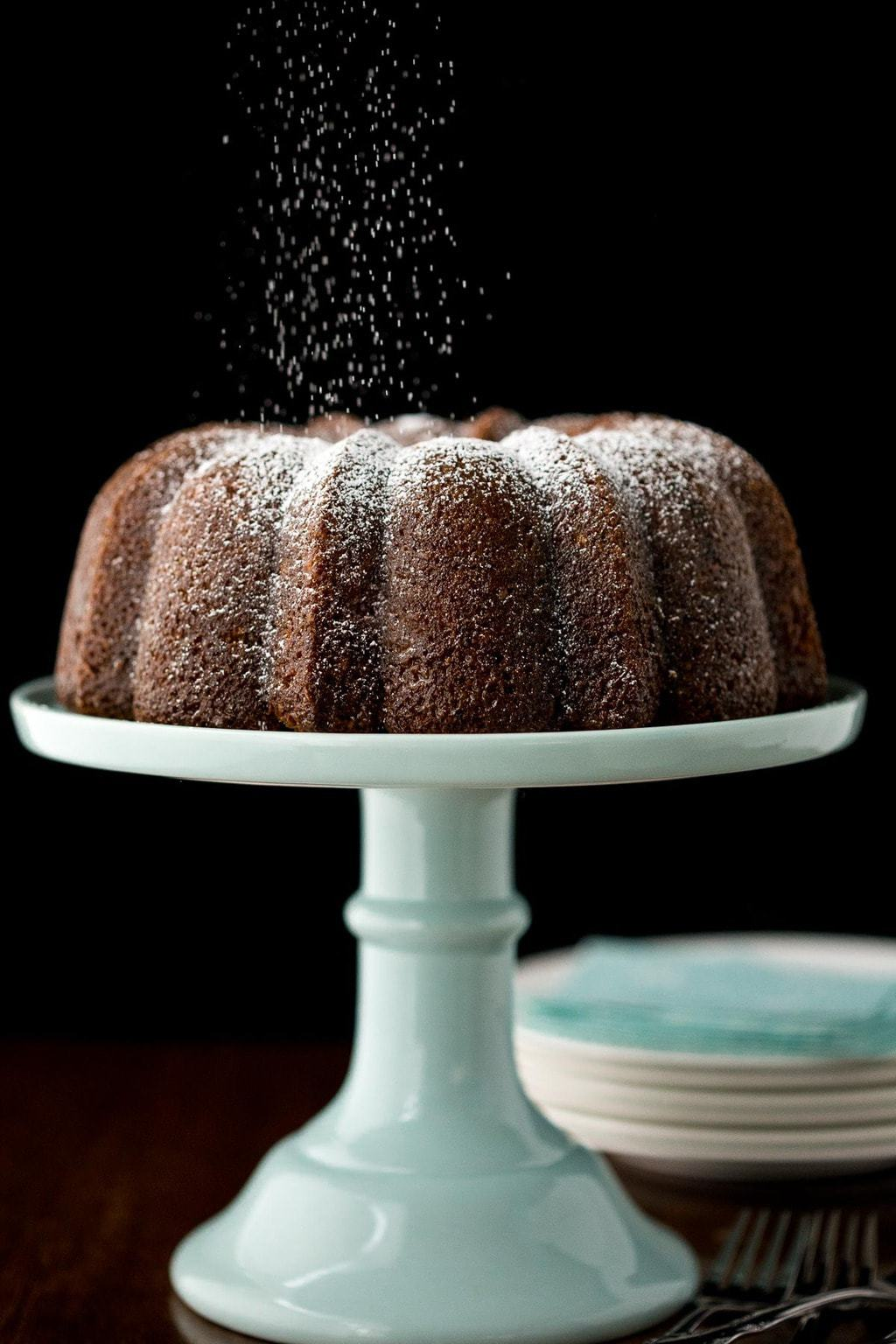 Vertical photo of Easy Carrot Bundt Cake on a turquoise cake stand being showered with powdered sugar against a black background.