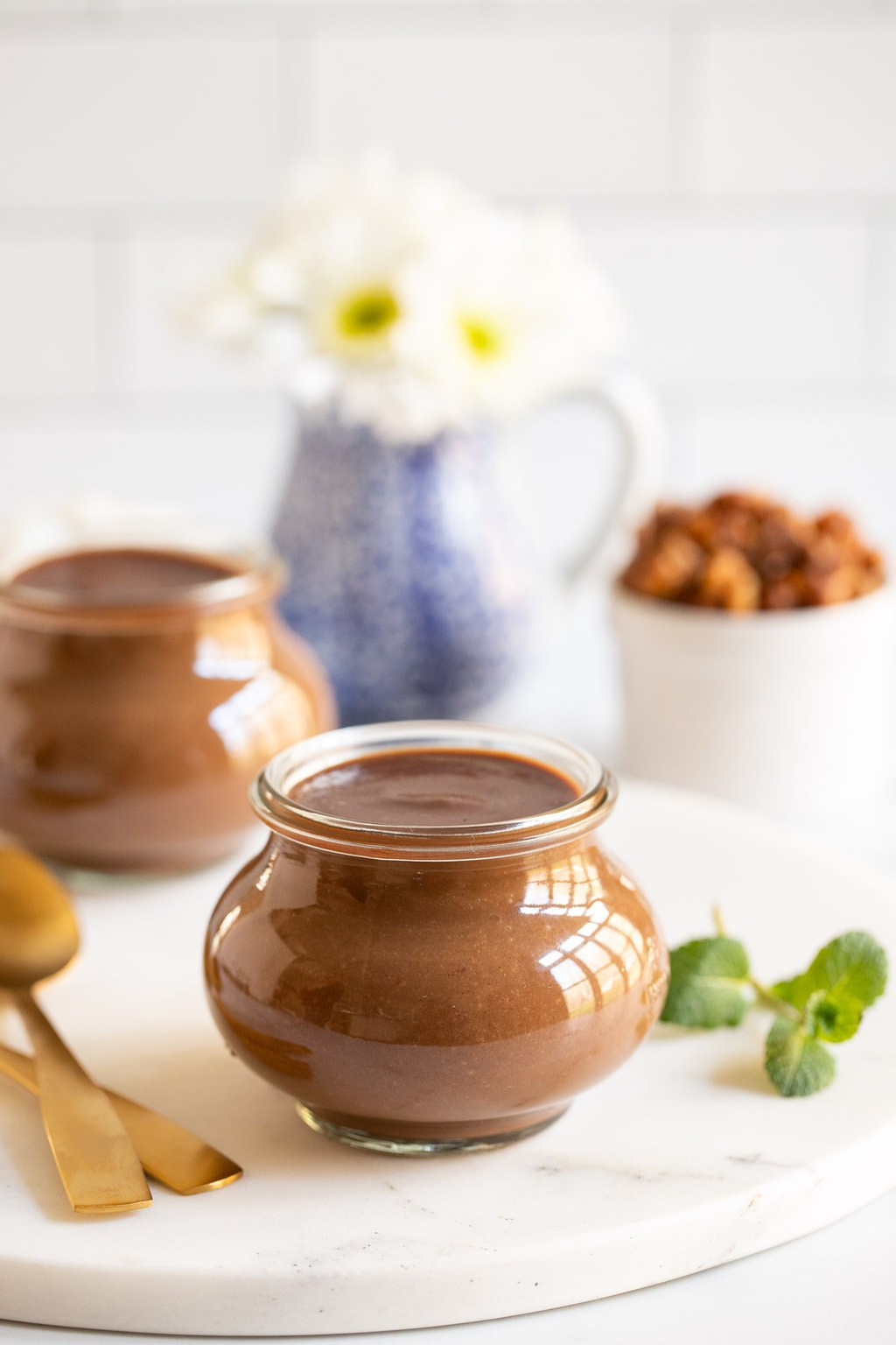 Vertical photo of Easy Chocolate Budino in glass Weck jars with a cup of candied maple walnuts in the background.