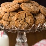 Vertical picture of ginger molasses cookies piled on a cake stand