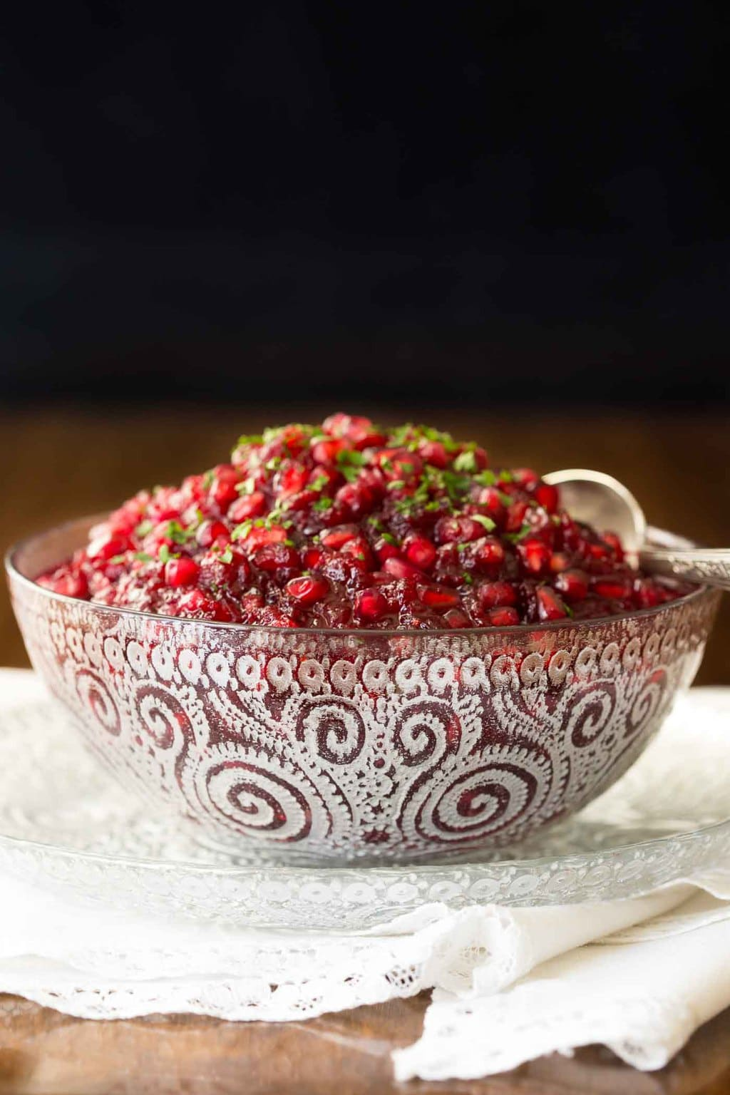 Photo of an etched glass bowl of Easy Cranberry Pomegranate Sauce on a white napkin sitting on a wood table.