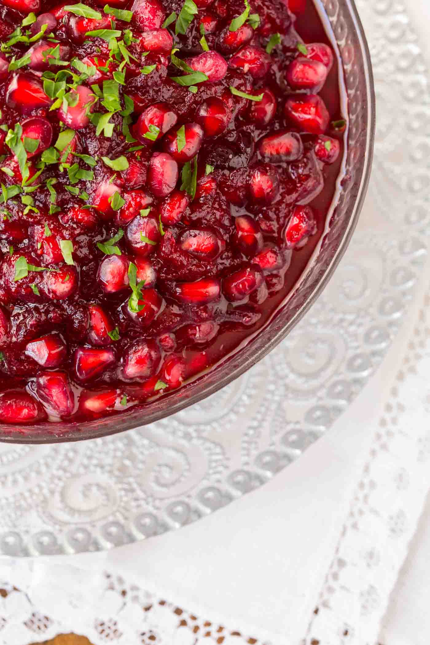 Overhead photo of an etched glass bowl of Easy Cranberry Pomegranate Sauce garnished with cilantro on a white decorative napkin.