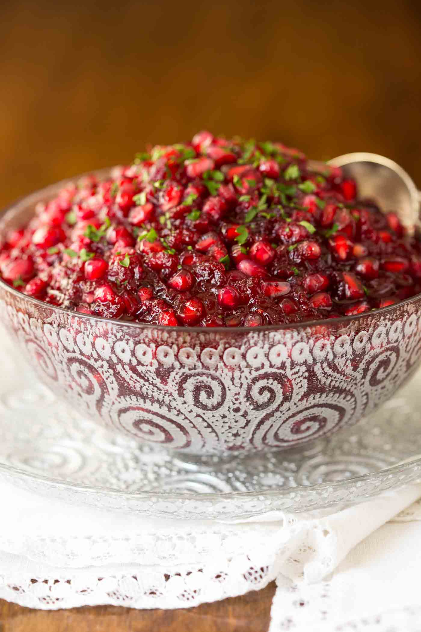 Photo of an etched glass bowl of Easy Cranberry Pomegranate Sauce on a saucer sitting on a wood table.