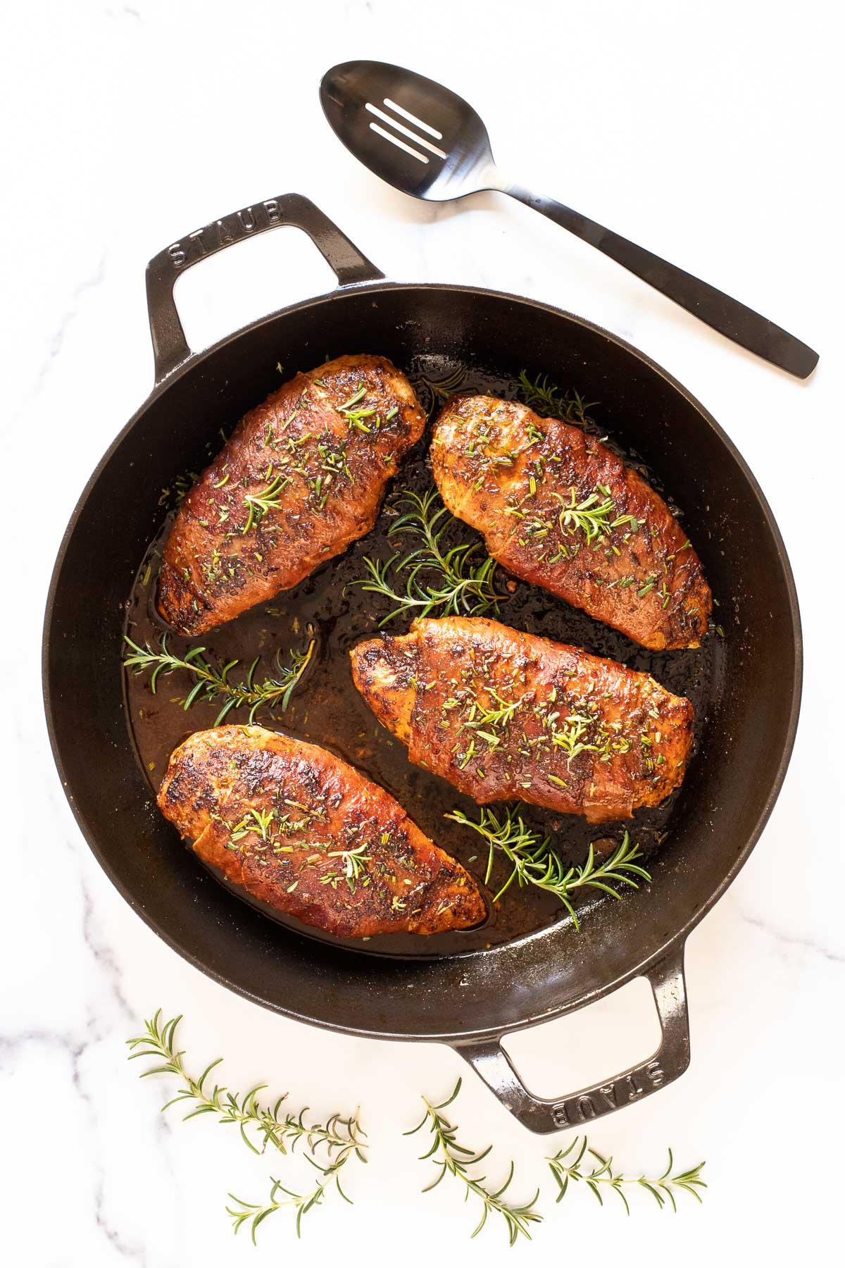 Vertical overhead photo of Prosciutto-Wrapped Chicken Breasts in a cast iron Staub frying pan.