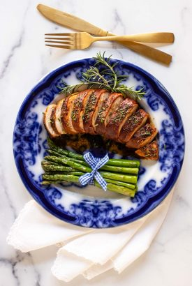 Overhead vertical photo of a plate of Prosciutto-Wrapped Chicken Breasts on a blue plate with grilled asparagus spears as a side.