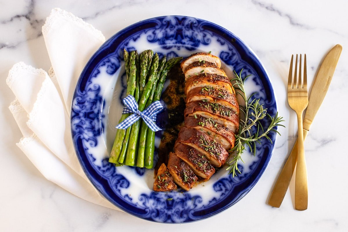 Horizontal overhead photo of a flow blue plate with Prosciutto-Wrapped Chicken Breasts and grilled asparagus spears.