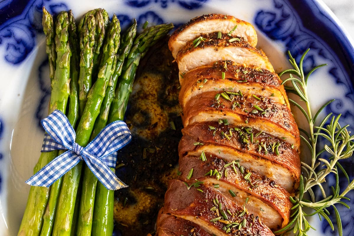 Overhead horizontal extreme closeup photo of Prosciutto-Wrapped Chicken Breasts on a plate with asparagus spears.