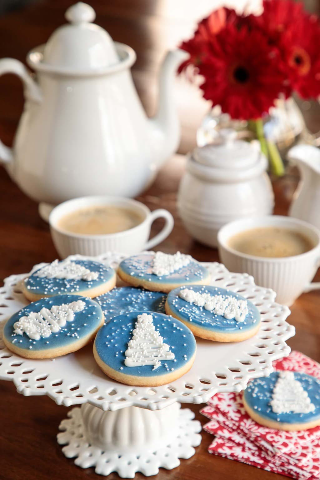 Photo of a white laced presentation plate filled with Easy Decorated Christmas Cookies. A white ironstone coffee pot, red flowers and cups of coffee are in the background.