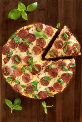 Overhead picture of deep dish pepperoni pizza on a wooden cutting board