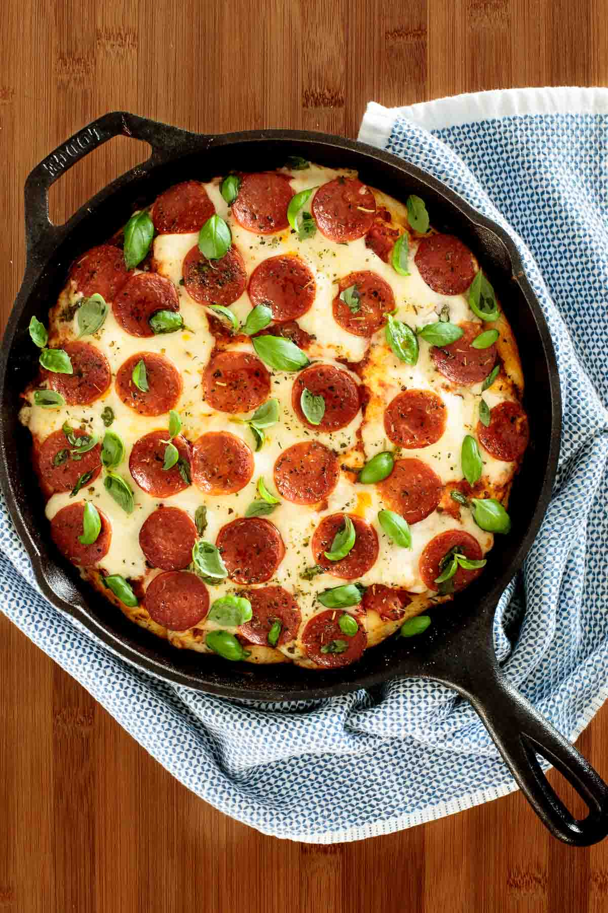 Overhead photo of an Easy Deep Dish Pepperoni Pizza baked in a cast iron skillet resting on a wood cutting board and surrounded by a blue and white towel.