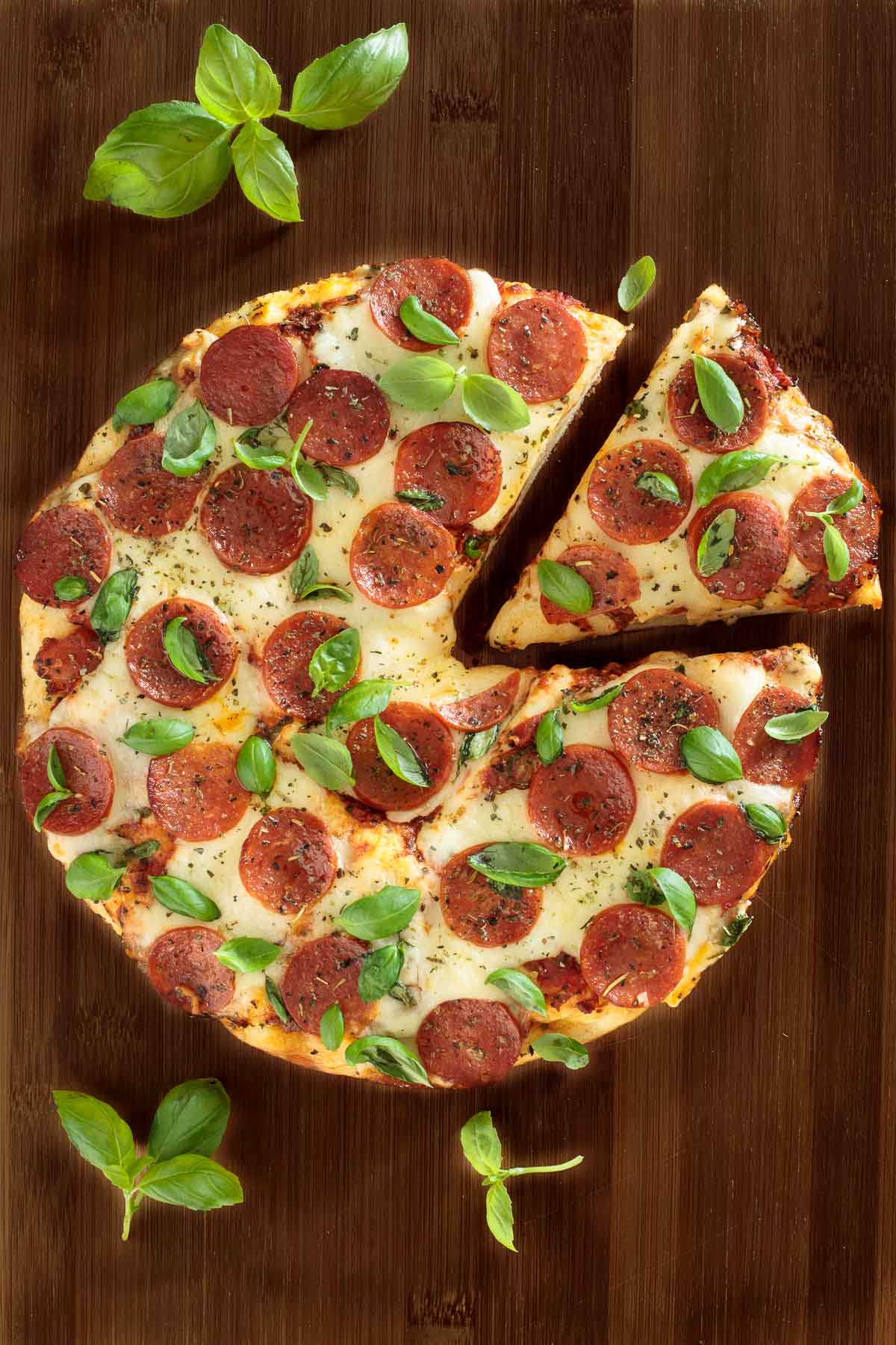 Overhead photo of an Easy Deep Dish Pepperoni Pizza on a wood table with a slice pulled out. Fresh basil garnishes surround the pizza.
