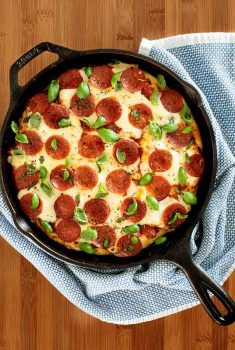 Overhead picture of deep dish pepperoni pizza in a cast iron skillet