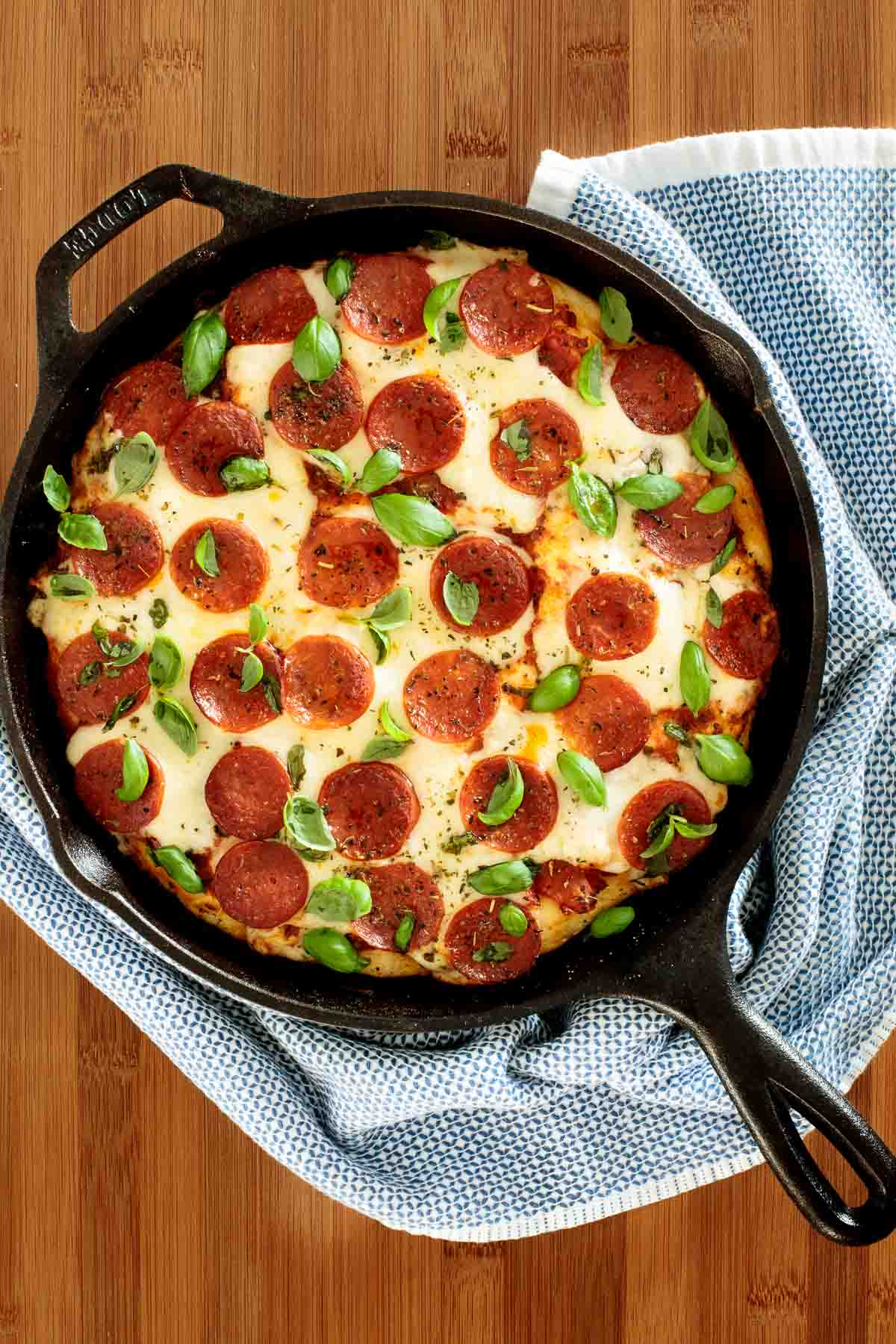 Overhead photo of Deep Dish Pepperoni Pizza in a cast iron skillet featuring a Deep Dish Pizza Crust.