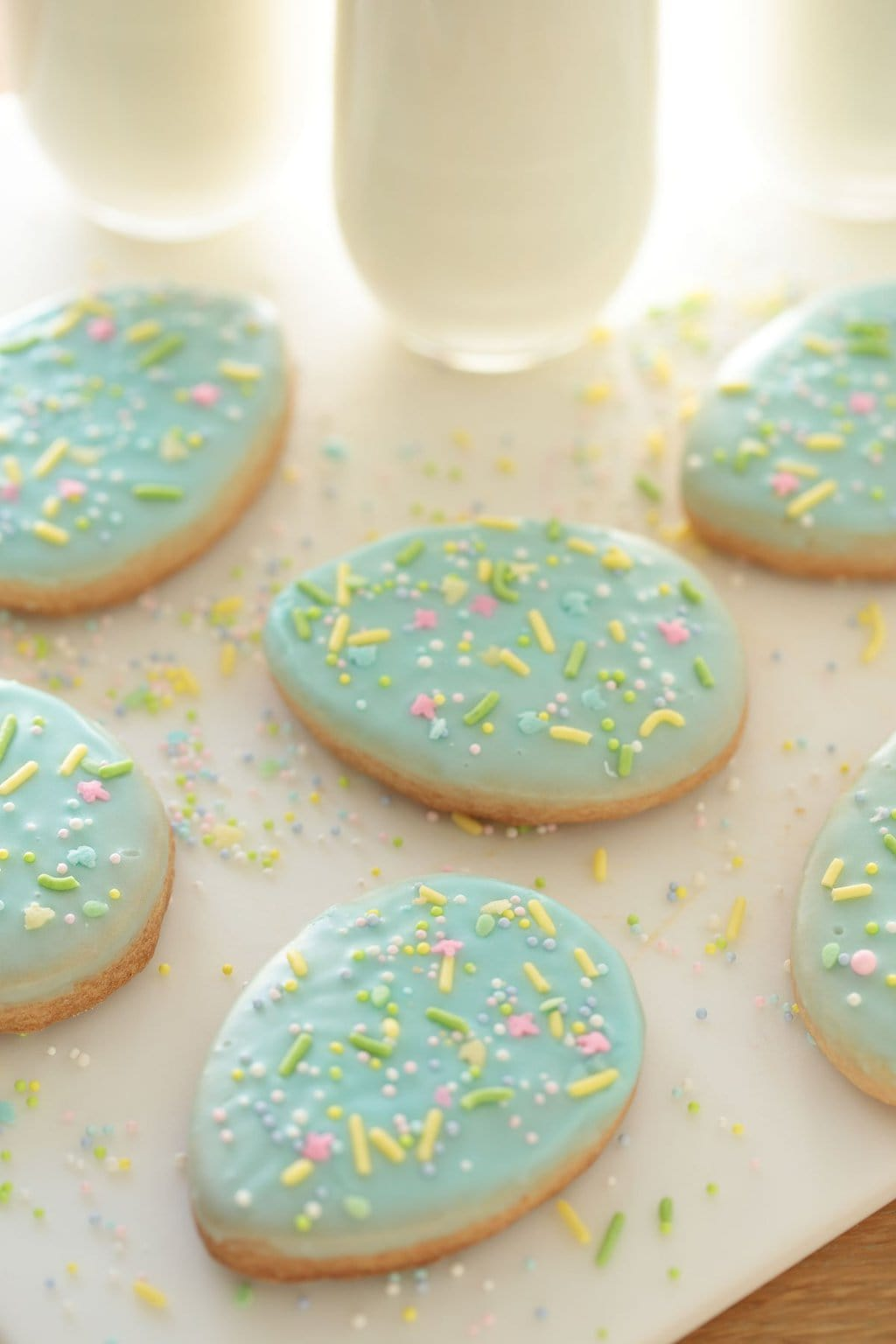 Vertical photo of decorated Spring Shortbread Cookies with sprinkles on a white surface.