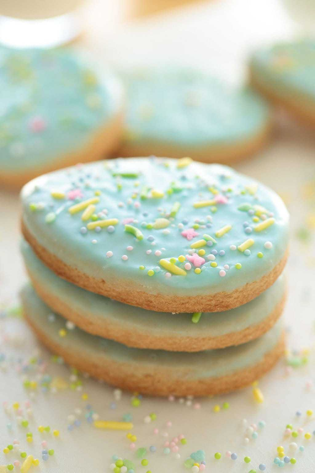 Ultra closeup photo of a stack of three Spring Shortbread Cookies on a white surface with pastel sprinkles all around.