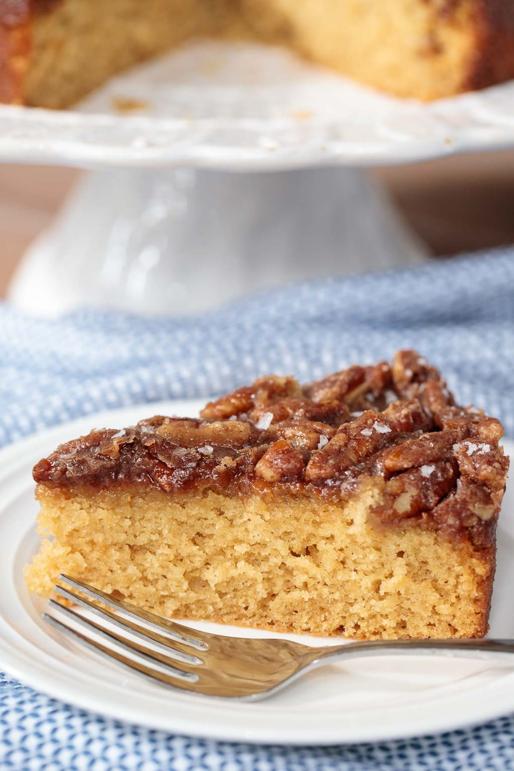 Vertical picture of Easy Farmhouse Buttermilk Cake on a blue and white napkin
