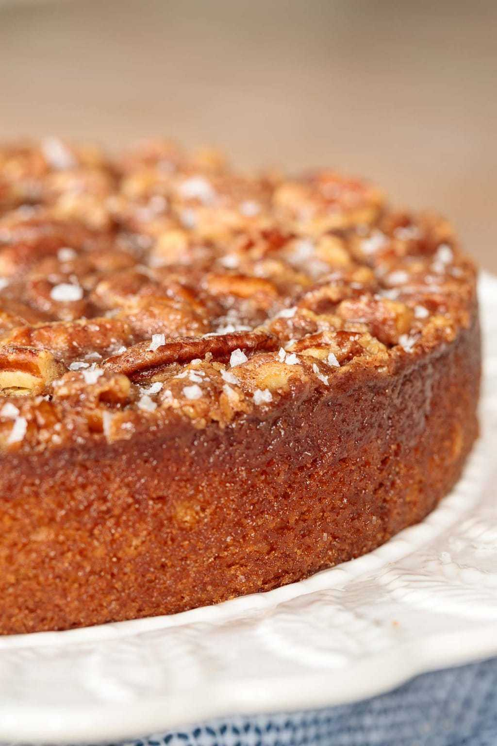 close up side view of buttermilk cake with candied pecan topping and sea salt