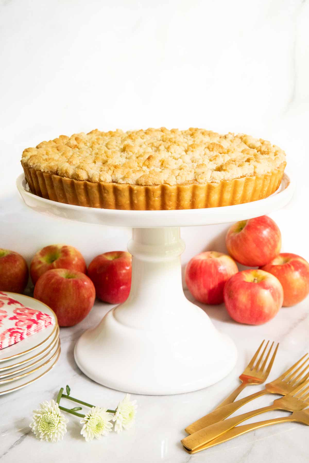 Vertical photo of a Easy French Apple Tart on a white pedestal presentation platter with fresh apples in the background.