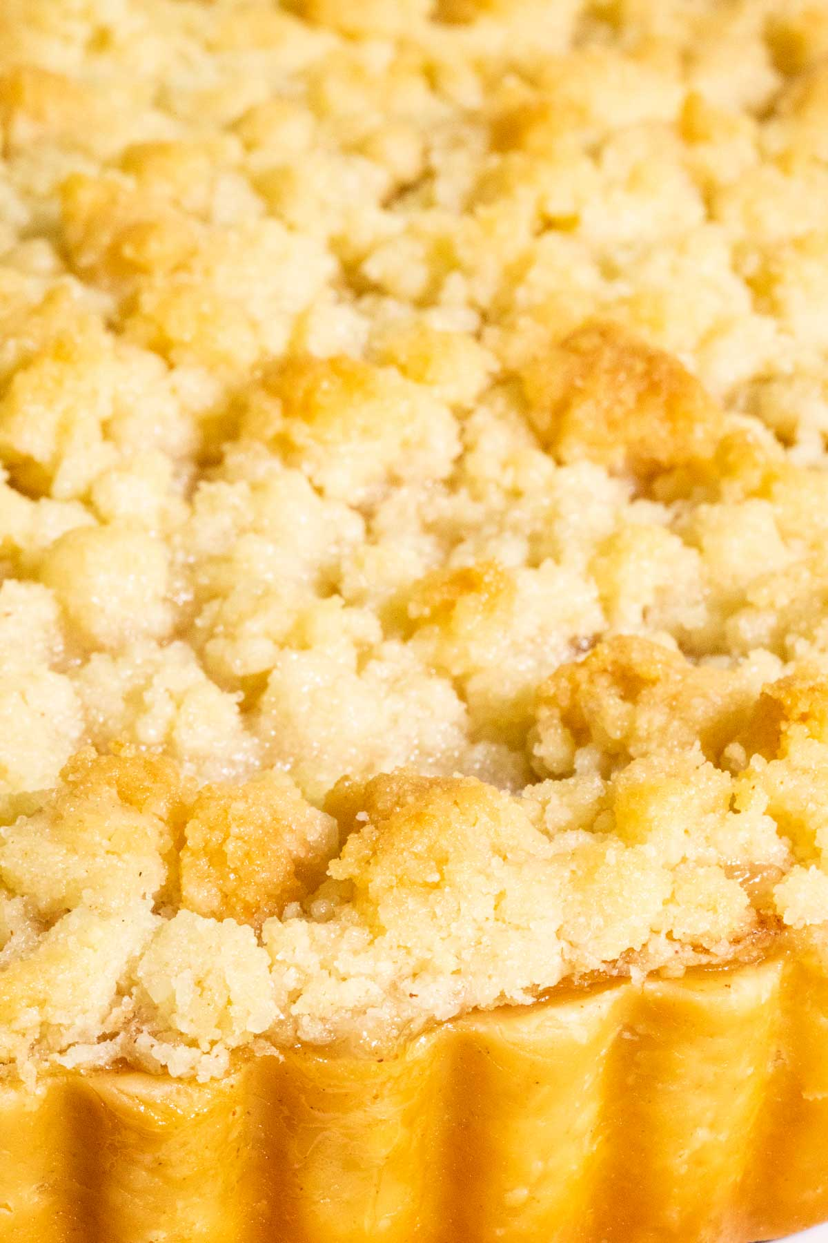 Vertical extreme closeup of the top crumble crust of an Easy French Apple Tart.