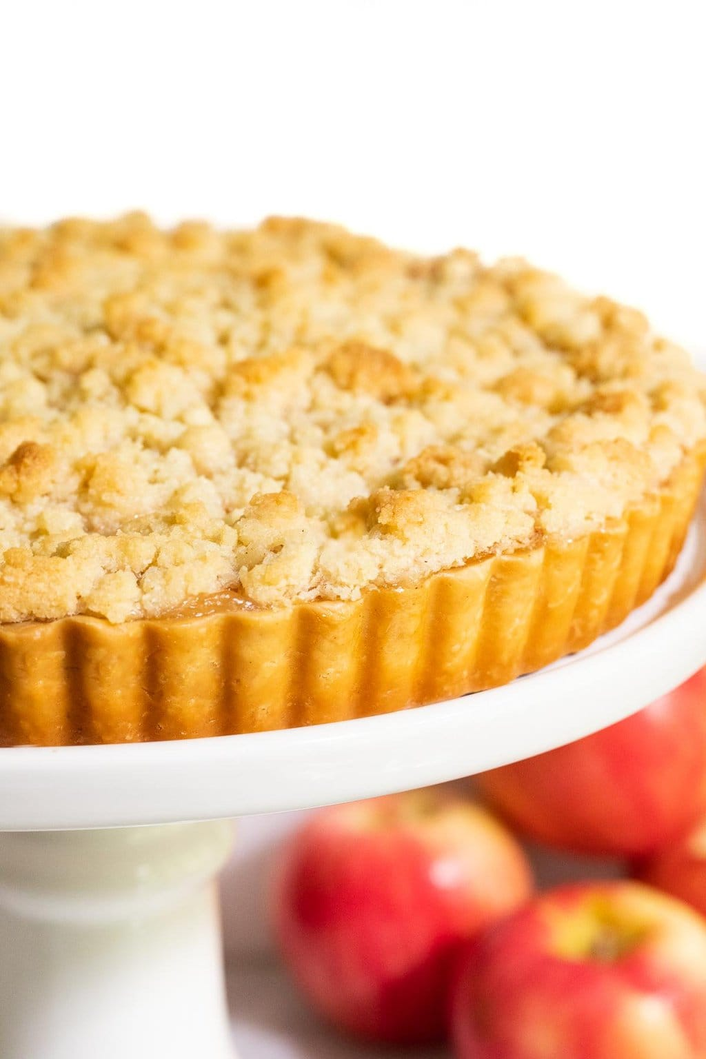 Vertical tight closeup photo of an Easy French Apple Tart on a white pedestal plate with apples in the background.