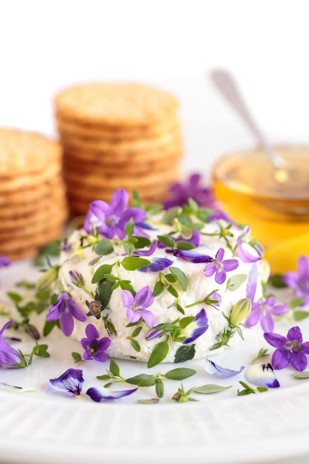 Closeup photo of an appetizer plate featuring the Easy Goat Cheese Appetizer decorated with tiny purple edible flowers. A small dish of honey and stacks of crackers are in the background.