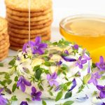 Vertical picture of goat cheese, edible flowers and crackers