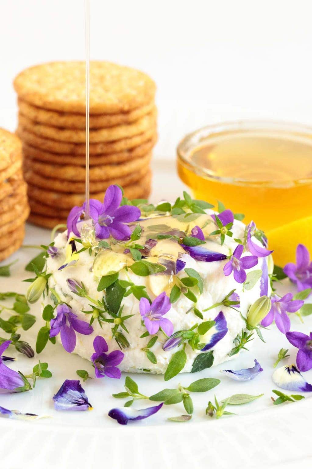 Vertical photo of an Easy Goat Cheese Appetizer covered in edible flowers with stacks of crackers and a bowl of honey in the background.
