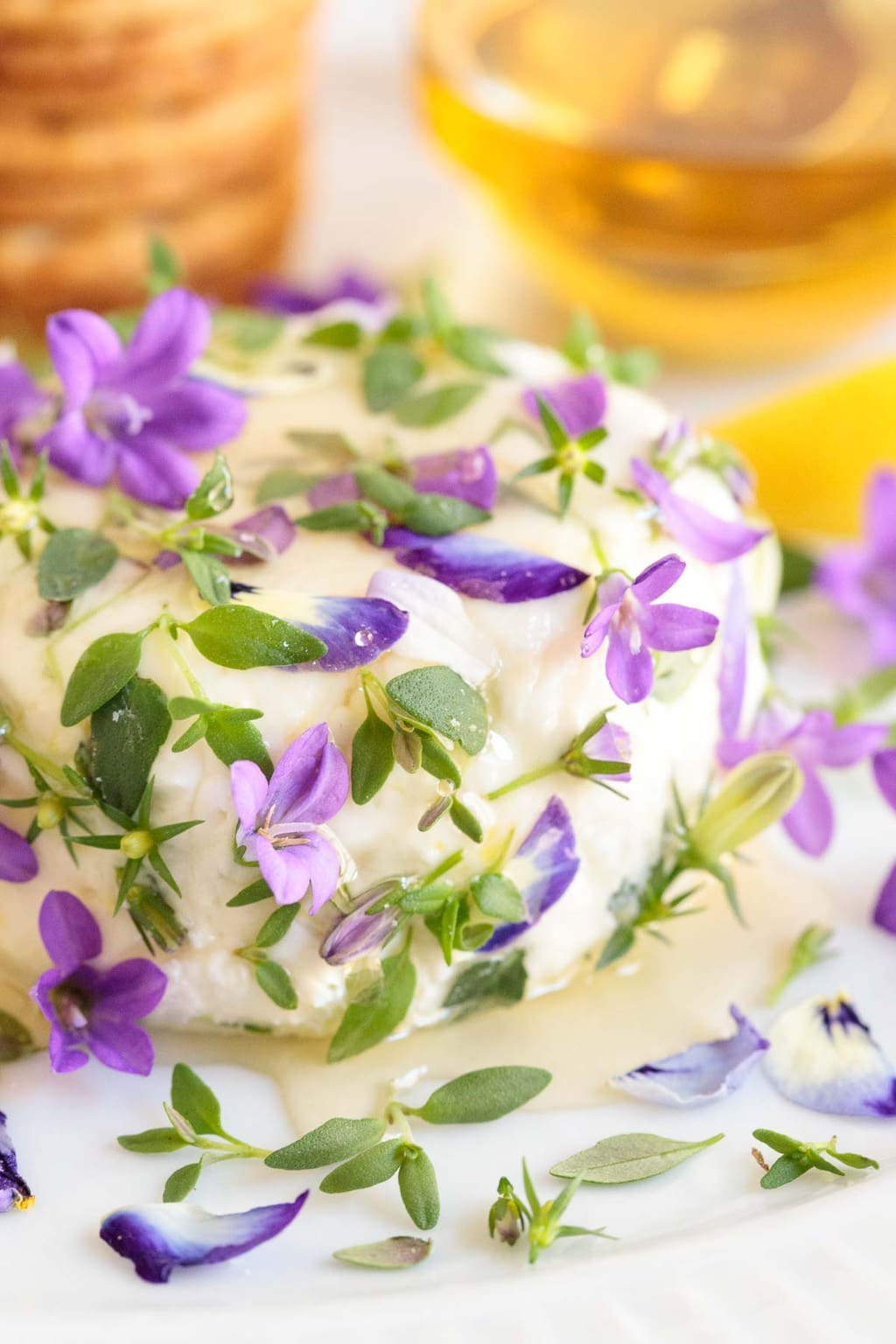 Ultra closeup photo of an Easy Goat Cheese Appetizer decorated with purple edible flowers, blossoms and buds.