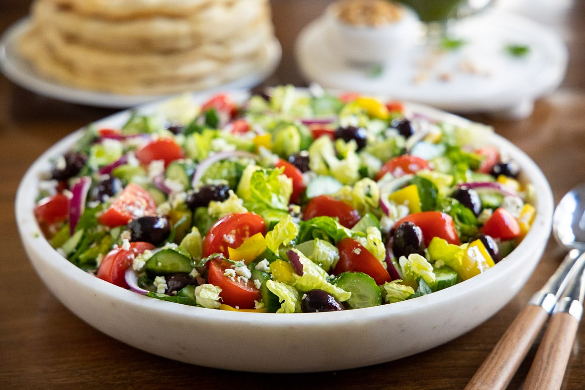Horizontal closeup photo of a white marble bowl of salad with Easy Greek Salad Dressing with Fresh Herbs on top.