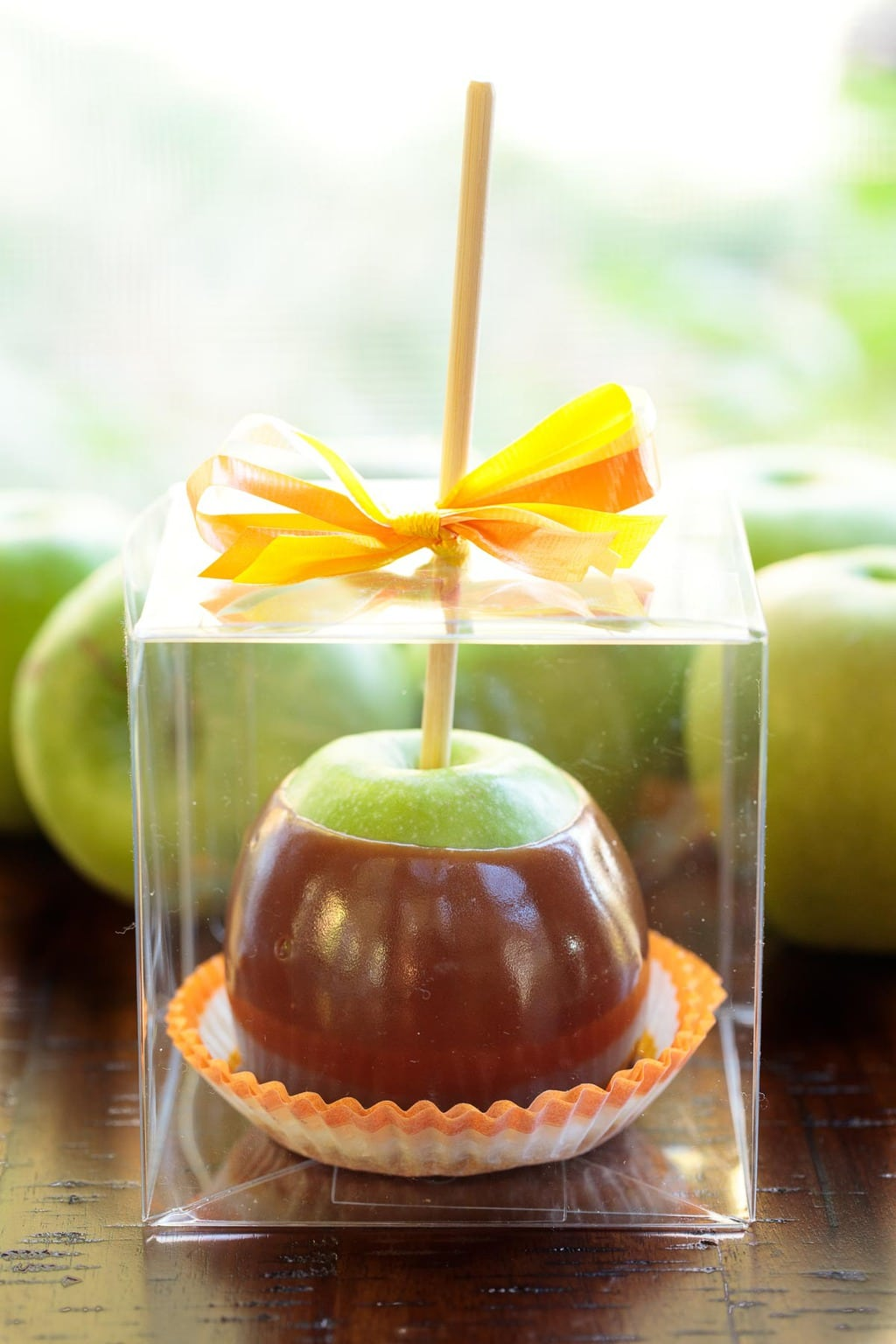Photo of an Easy Homemade Caramel Apple in a decorative clear plastic container with an orange and yellow bow on top.
