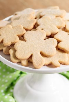 Vertical picture of easy Irish Shortbread shamrock cookies on a white cake stand