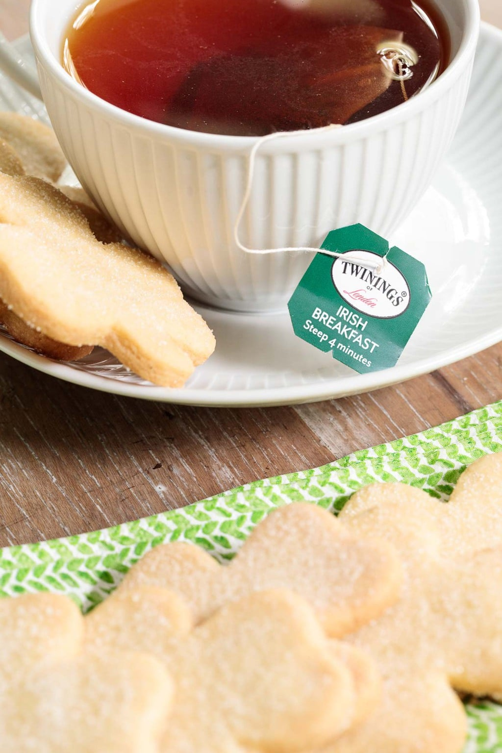 Closeup of a row of Easy Irish Shortbread Cookies with a cup of Twinnings Irish Breakfast tea in the background.