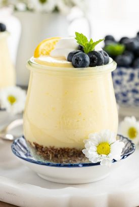 Vertical picture of Easy Lemon Curd Mouse in a small glass jar garnished with blueberries and flowers
