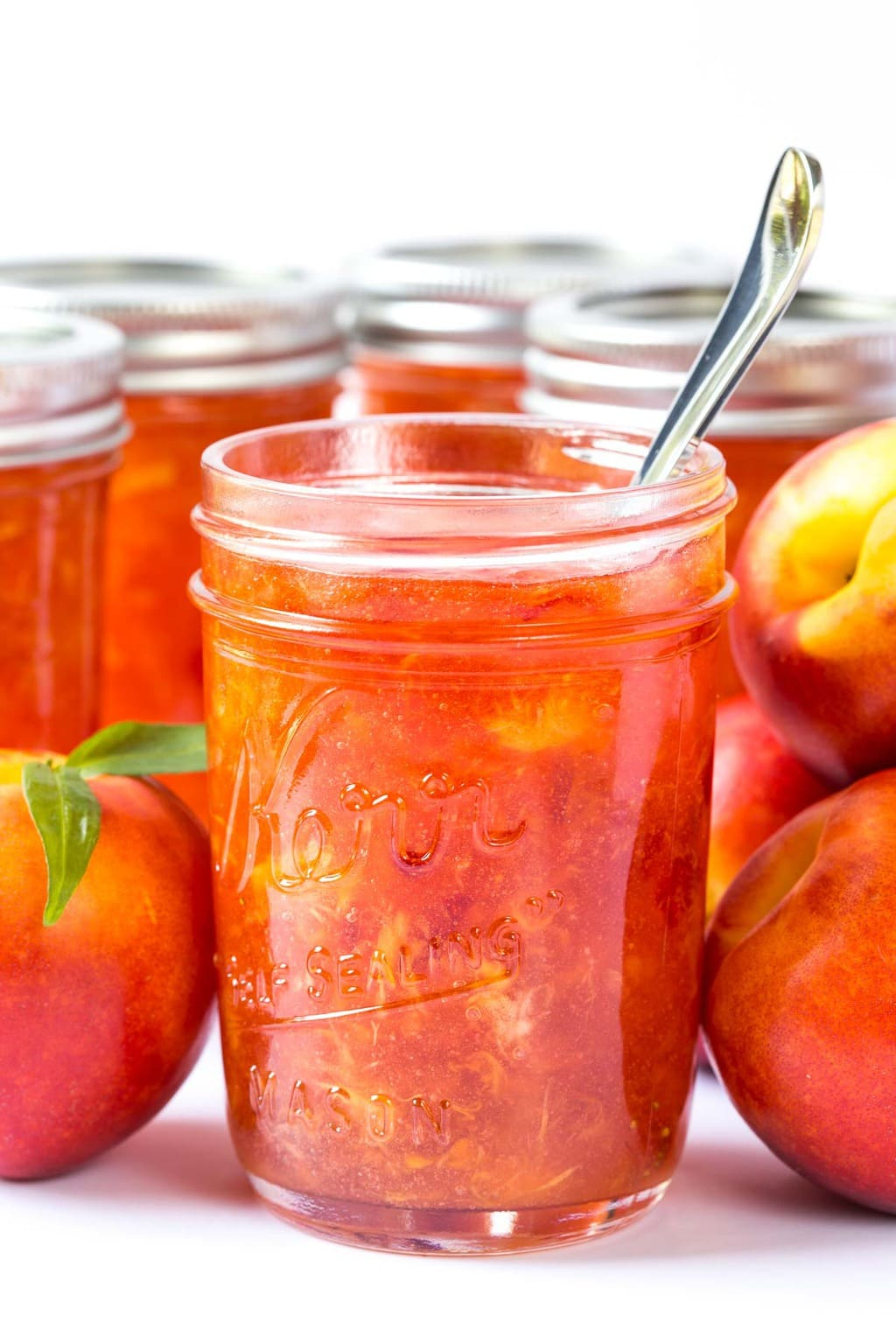 A photo of canning jars filled with peach freezer jam surrounded by fresh peaches.
