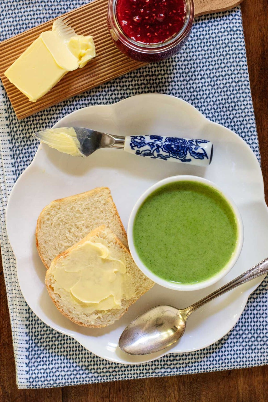 Overhead photo of a plate with slices of Overnight No-Knead Brioche Bread next to a cup of Fresh Spinach Soup with jelly and jam.