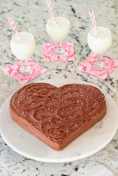 Vertical picture of a chocolate heart cake with glasses of milk