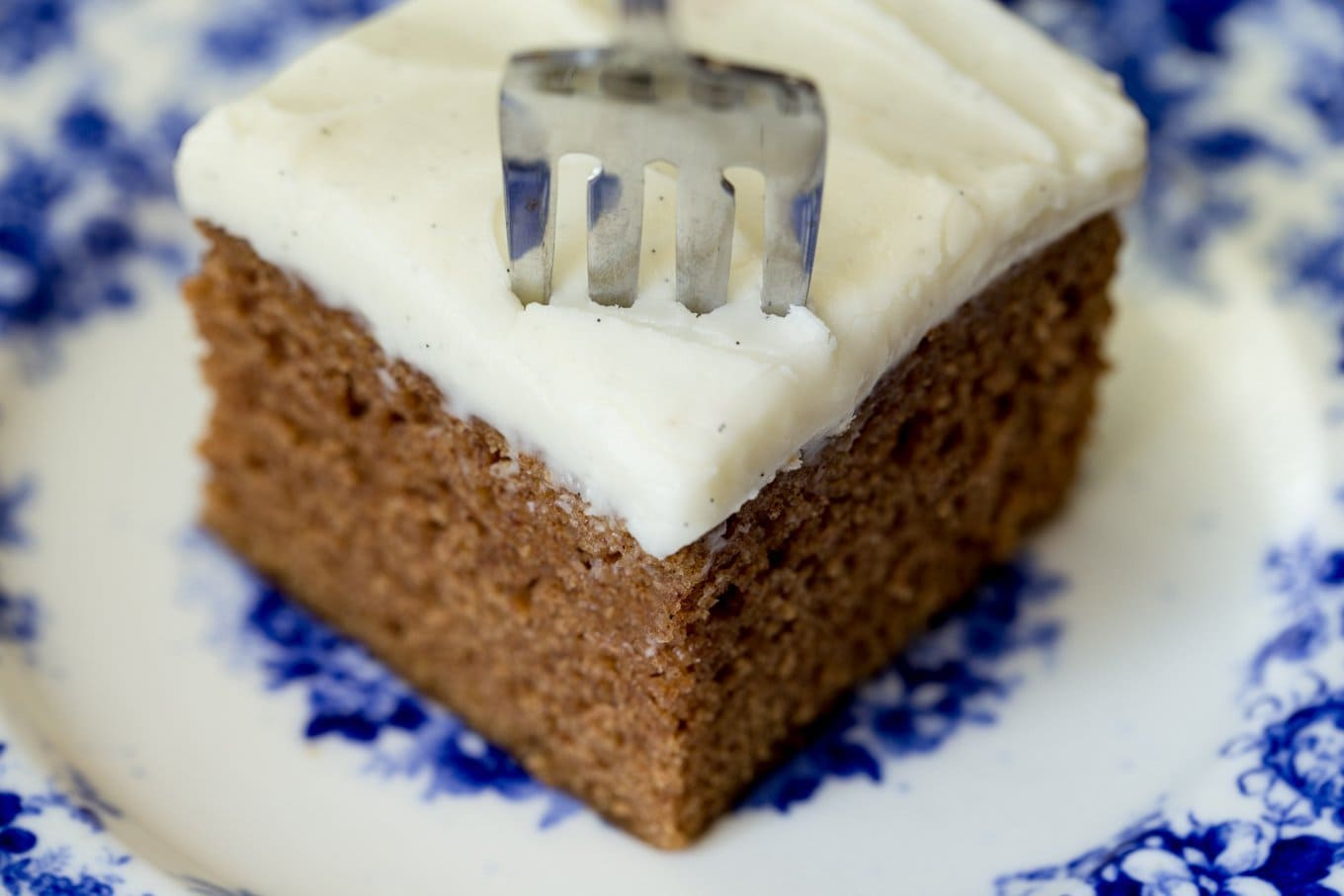 Closeup photo of a piece of Easy Gingerbread Cake with Vanilla Bean Icing on a delft blue patterned plate.