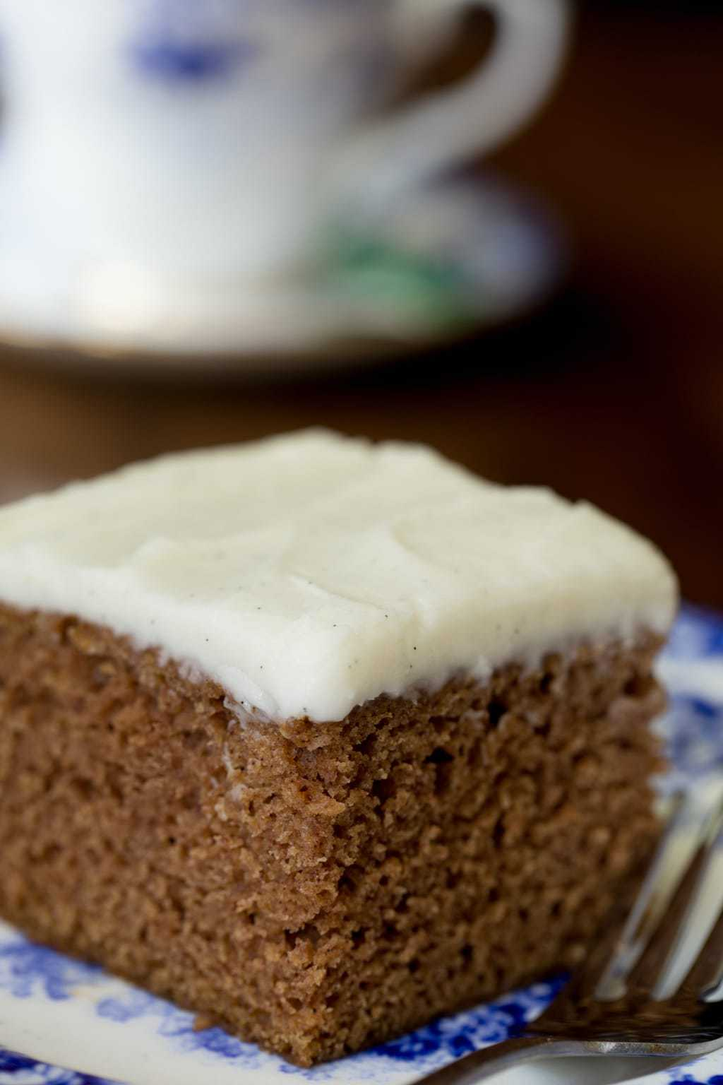 Photo of a piece of Easy Gingerbread Cake with Vanilla Bean Icing on a delft blue patterned serving plate.