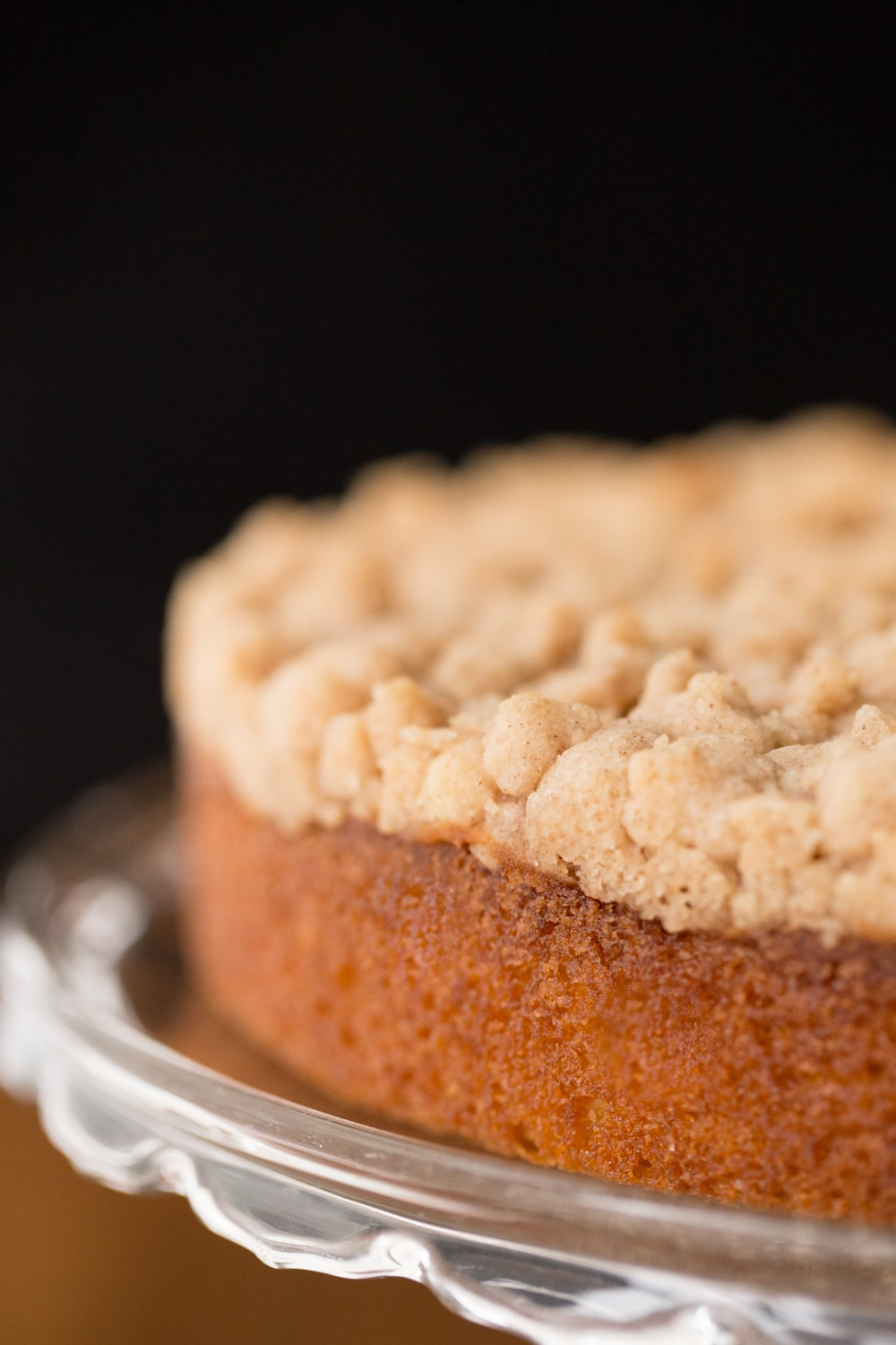 Vertical closeup photo of Easy Overnight Coffee Cake on a glass cake stand.