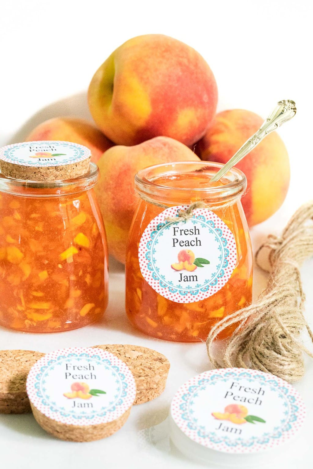 Vertical photo of jars of Easy Peach Freezer Jam complete with different styles of caps in the foreground and fresh peaches in the background.