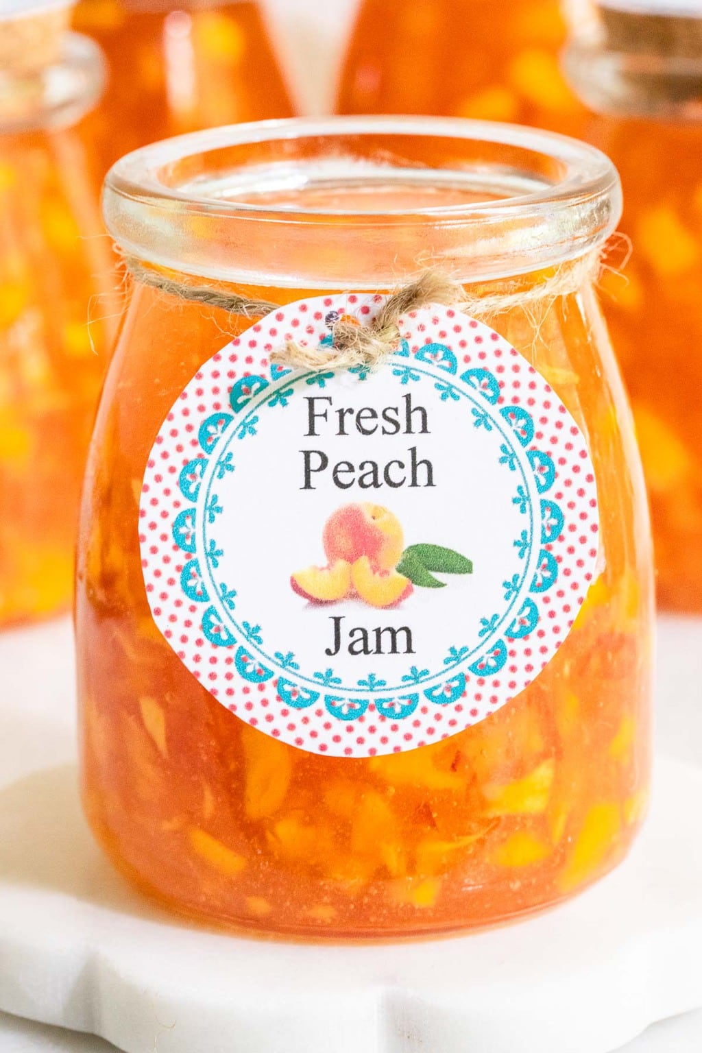 Extreme vertical closeup photo of a jar of Easy Peach Freezer Jam with a label attached to the front of it.