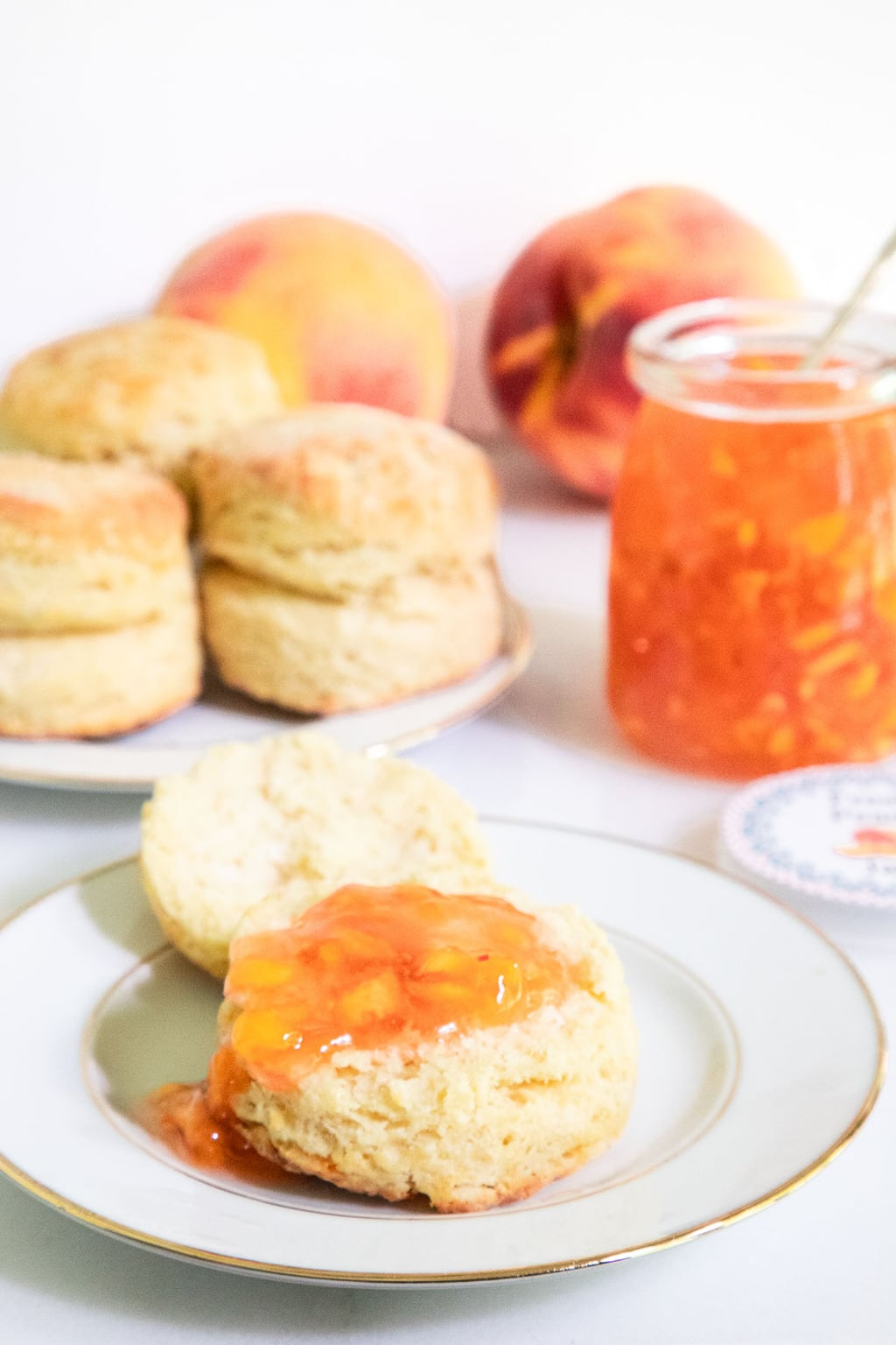 Vertical photo of a biscuit served with Easy Peach Freezer Jam spread over the top.