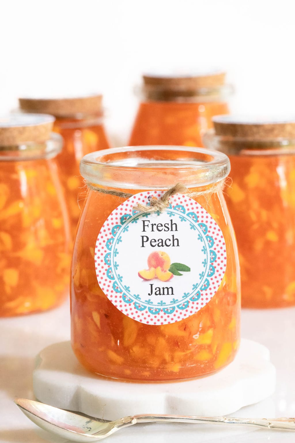 Vertical closeup photo of a glass jar of Easy Peach Freezer Jam with a colorful label tied to it and more jars in the background.