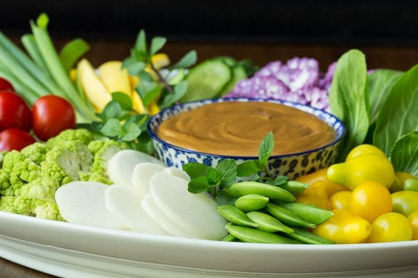 An assortment of veggies on a white platter with a blue and white bowl of Easy Peanut Sauce in the center.
