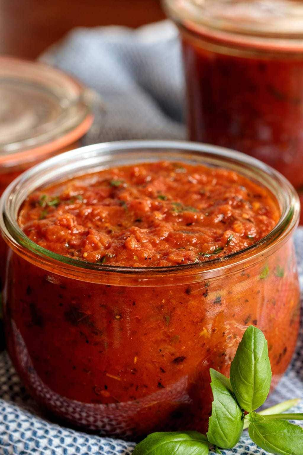 Photo of a glass Weck jar filled with Super Easy Pizza Sauce with a fresh basil leave in front of the jar.