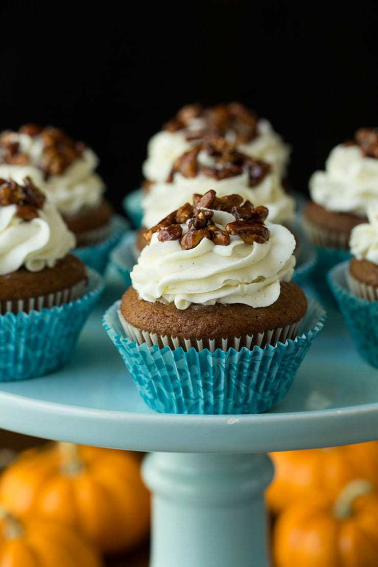 Vertical close up photo of Easy Pumpkin Cupcakes on a turquoise presentation stand.