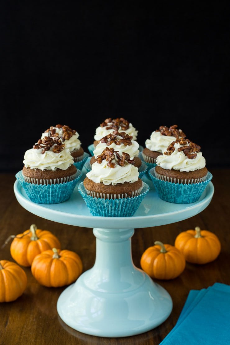 Photo of a light blue pedestal plate filled with Easy Pumpkin Cupcakes. Mini pumpkins surround the plate on a wood table.