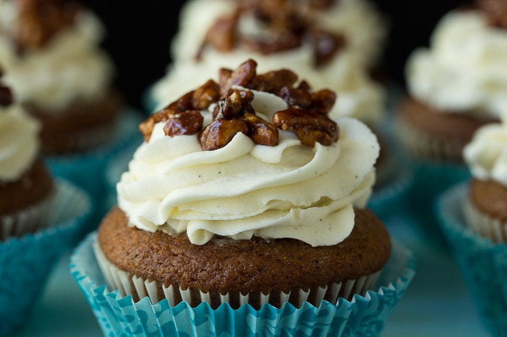 Closeup photo of a plate of Easy Pumpkin Cupcakes with vanilla bean buttercream frosting and easy candied pecans on top in white and turquoise cupcake papers.
