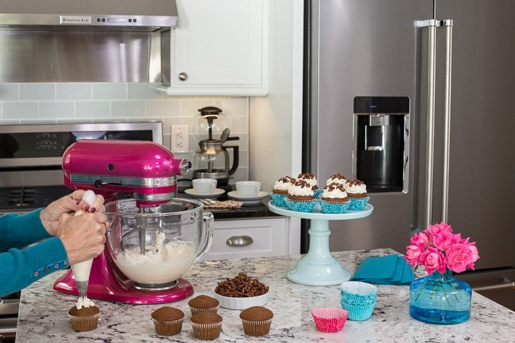 Photo of a kitchen with KitchenAid appliances featuring a KitchenAid Susan Komen Pink stand mixer and a person putting icing on Easy Pumpkin Cupcakes