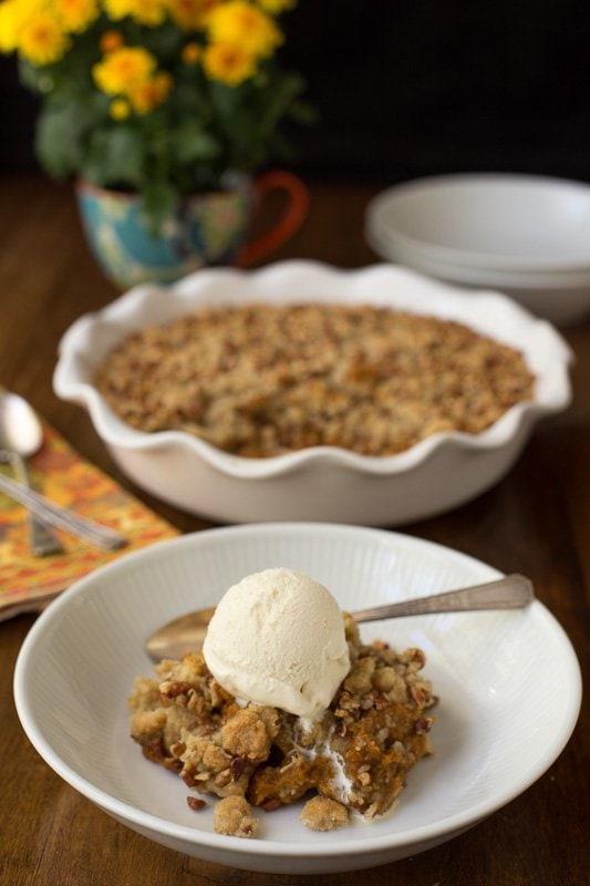 Vertical photo of Easy Pumpkin Praline Cobbler in a white bowl with vanilla ice cream.