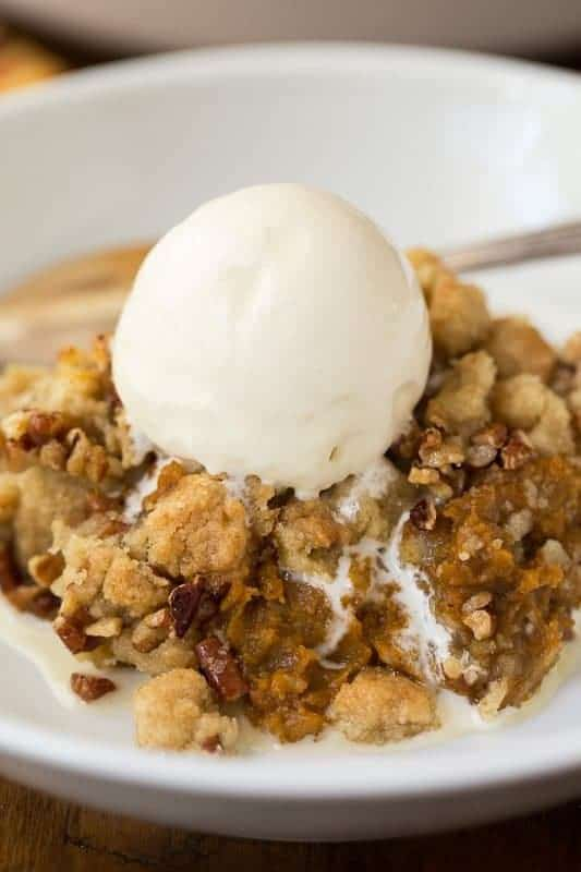 A closeup photo of a dish of Easy Pumpkin Praline Cobbler with a scoop of ice cream melting on top.